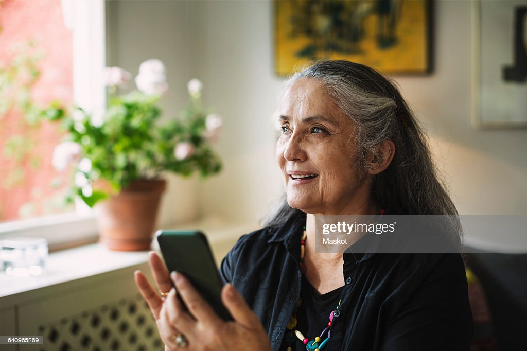 Happy senior woman using mobile phone at home : Stock Photo