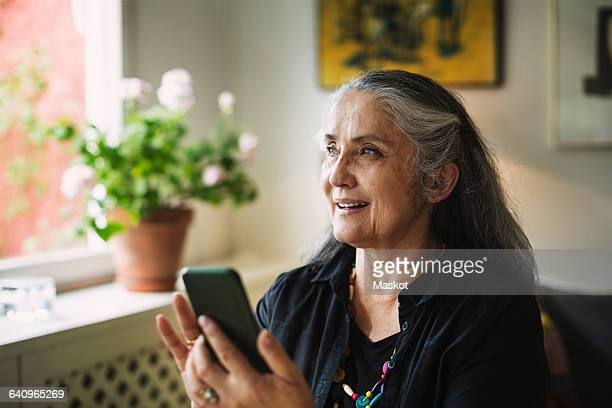 happy senior woman using mobile phone at home - home icon stock photos and pictures