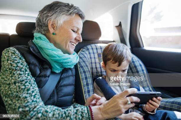 Happy senior woman using smart phone with grandson in car
