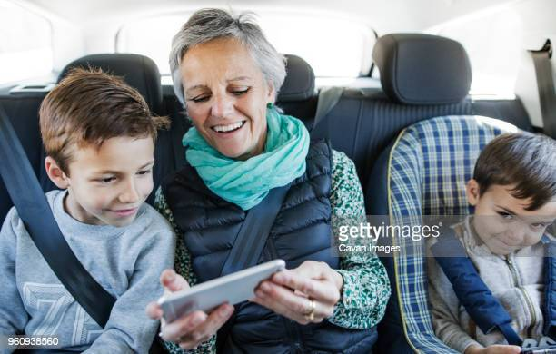 Happy senior woman using smart phone with grandsons in car