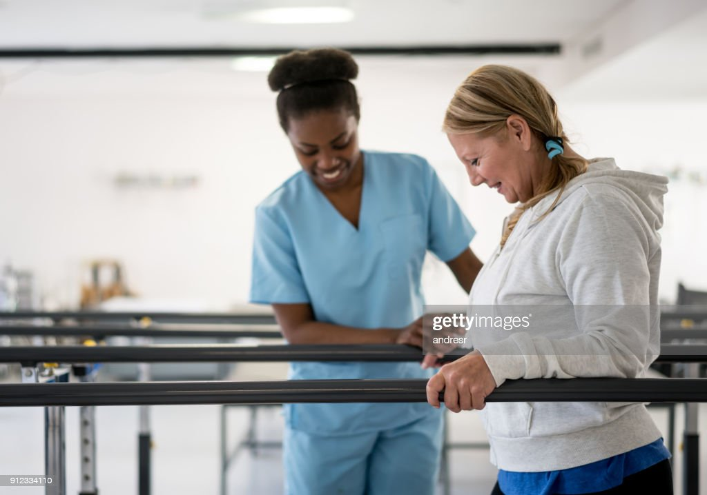 Happy senior woman walking between parallel bars at physiotheray with her therapist next to her : Stock Photo