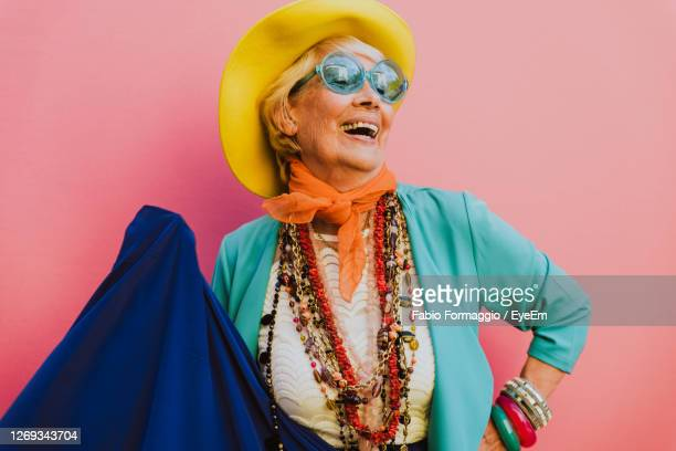happy senior woman wearing jewelries against pink background - multi colored hat stock pictures, royalty-free photos & images
