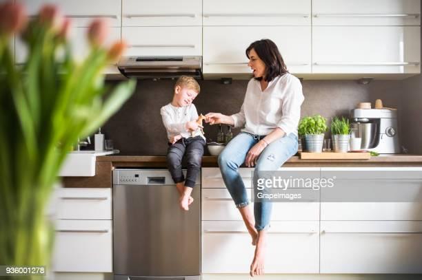 Heureuse femme senior avec un petit garçon dans la cuisine à la maison.