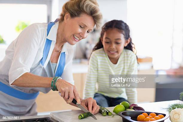 Happy senior woman with granddaughter in kitchen