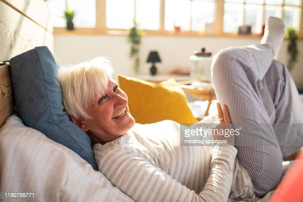 happy senior woman with gray hair lying in bed - nightdress stock pictures, royalty-free photos & images