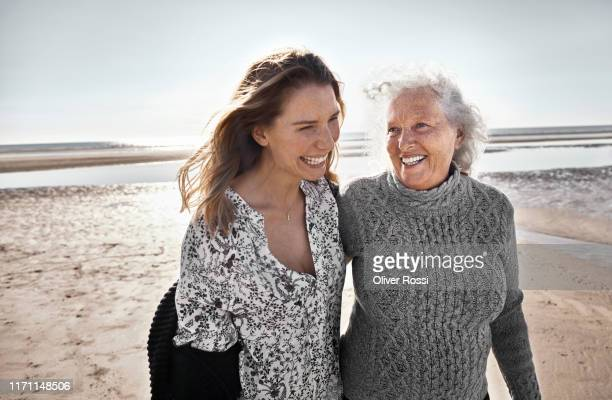 happy senior woman with her adult daughter on the beach - senior women stock pictures, royalty-free photos & images