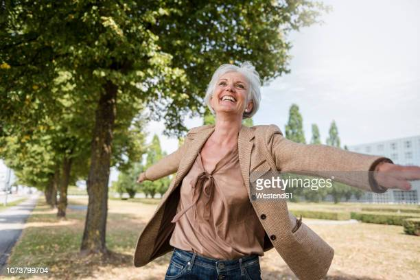 happy senior woman with outstretched arms in a park - 60 64 jahre stock-fotos und bilder