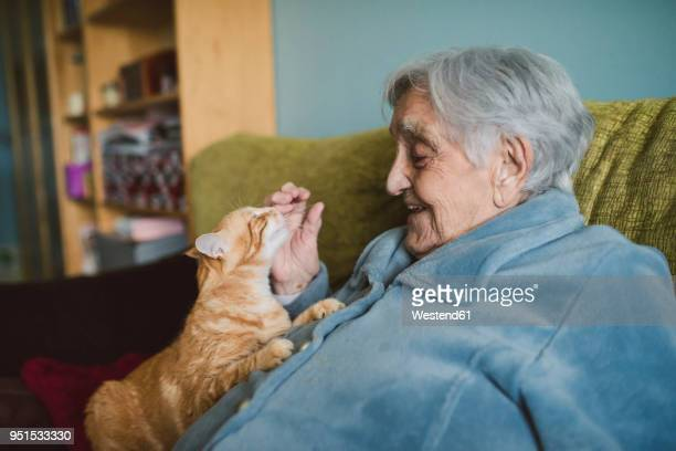 Happy senior woman with tabby cat on the couch