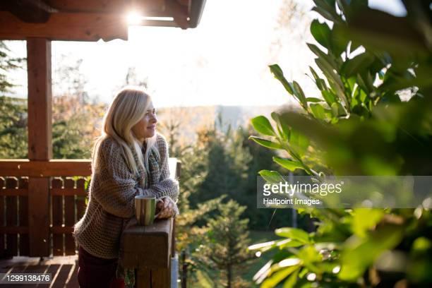 happy senior woman with tea outdoors on terrace in autumn, relaxing. - vivere semplicemente foto e immagini stock