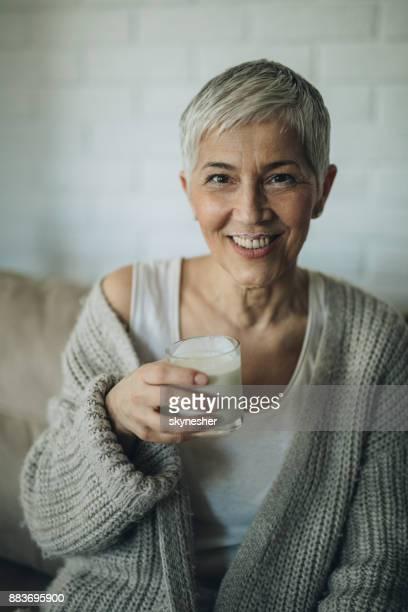 Happy senior woman with yogurt mustache at home.