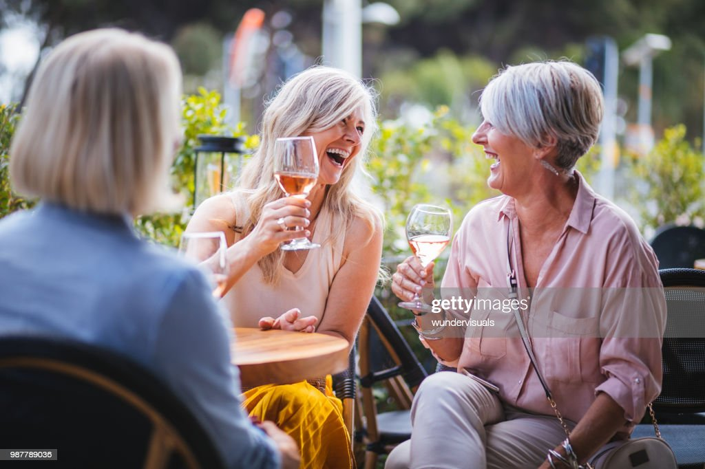 Happy senior women drinking wine and laughing together at restaurant : Stock Photo