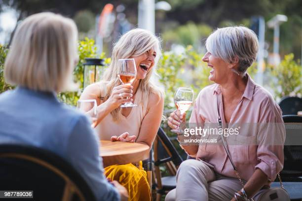 happy senior women drinking wine and laughing together at restaurant - mulheres maduras imagens e fotografias de stock