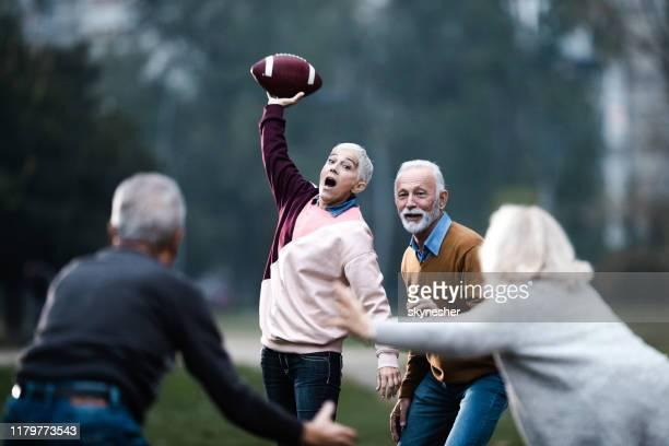 felices personas mayores divirtiéndose mientras juegan rugby en el parque. - rugby union fotografías e imágenes de stock