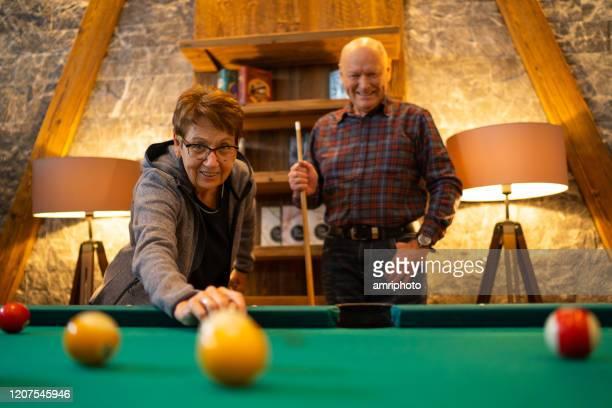 glückliche senioren spielen pool - poolbillard billard stock-fotos und bilder