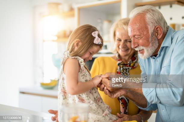 happy seniors playing with their granddaughter in the kitchen. - grandfather stock pictures, royalty-free photos & images