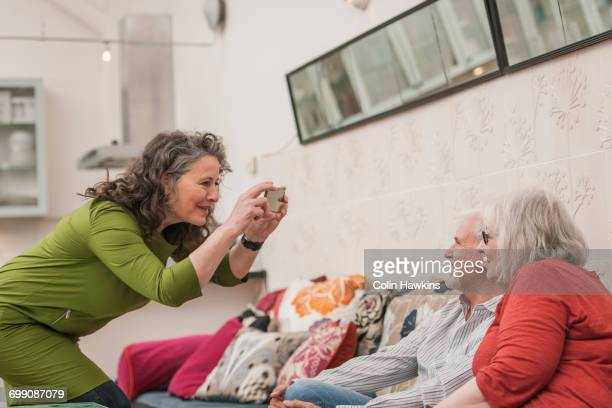 happy seniors taking photograph on couch - down blouse stock pictures, royalty-free photos & images