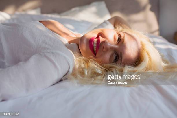 Happy sensuous woman looking away while lying on bed