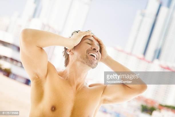 Happy shirtless Japanese man enjoying beach holiday