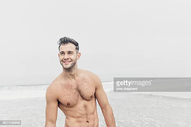 happy shirtless man at the beach.