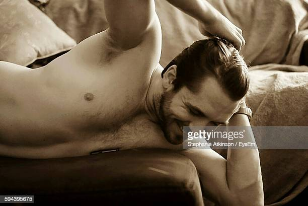 Happy Shirtless Man Relaxing On Bed