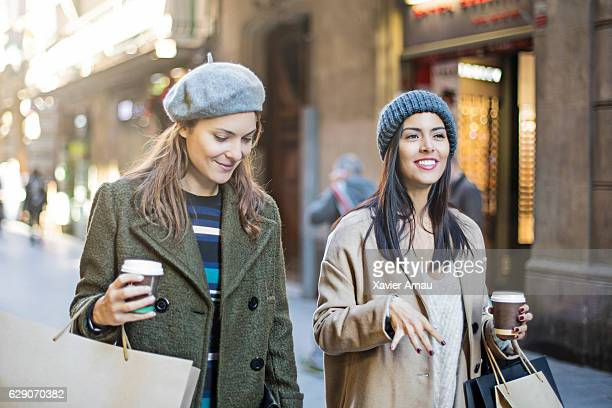Happy shopaholic friends walking on city street