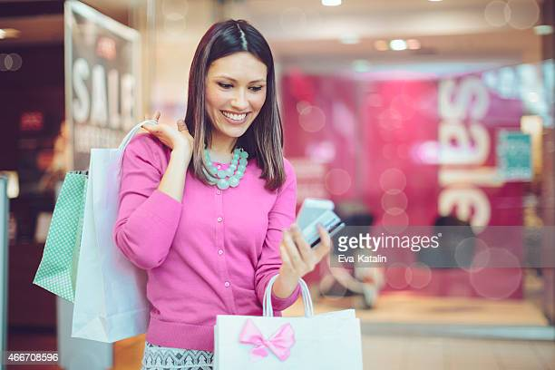 Happy shopper checking her messages on her cell phone