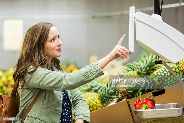 Happy shopper weighing produce