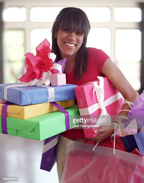 Happy shopper with armful of colorful wrapped packages