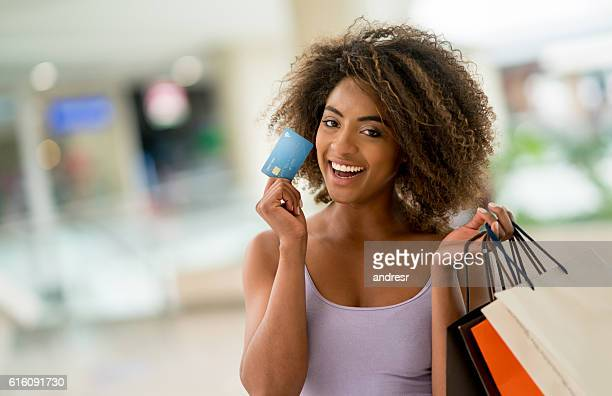 Happy shopping woman holding a credit card