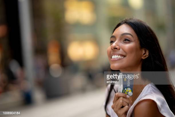 happy shopping woman holding a rewards card - coupon stock photos and pictures