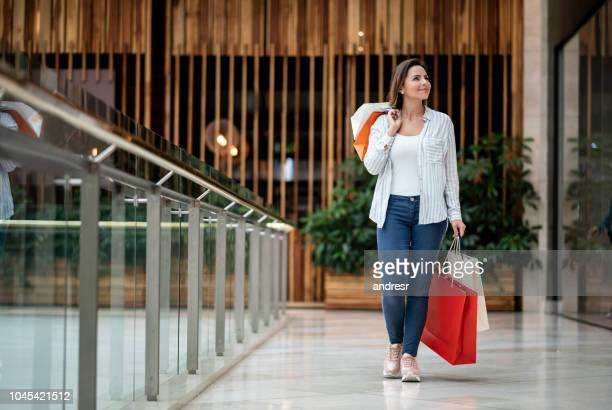 happy shopping woman holding bags at the mall - shopping centre stock pictures, royalty-free photos & images