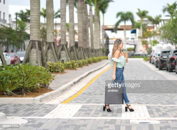 happy shopping woman outdoors holding bags - miami florida stock pictures, royalty-free photos & images