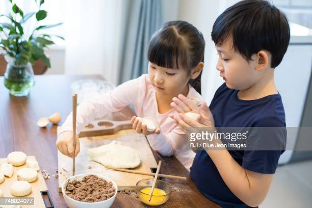 happy siblings baking together - moon cake stock pictures, royalty-free photos & images