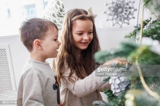 Happy siblings decorating Christmas tree at home