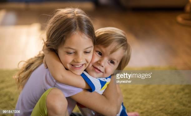 glücklich geschwister umarmen und zuneigung zueinander zu hause. - bruder stock-fotos und bilder