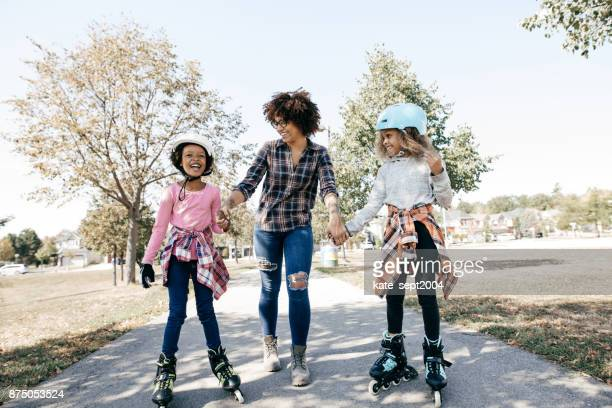 happy siblings on rollerblades - inline skating stock pictures, royalty-free photos & images