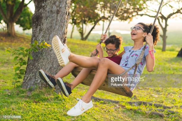 happy siblings playing on the swing - swing stock pictures, royalty-free photos & images