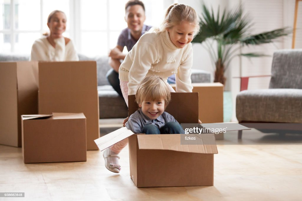 Happy siblings playing riding in box moving into new home : Stock Photo