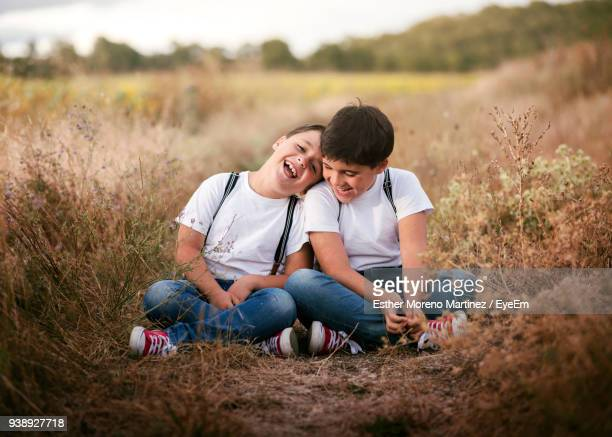 Happy Siblings Sitting On Field