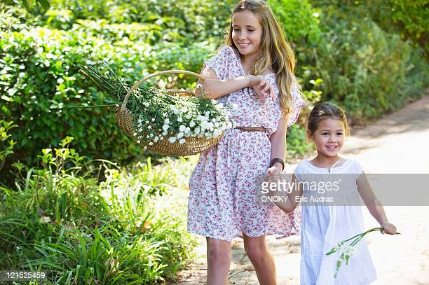 Happy siblings walking holding hands in garden