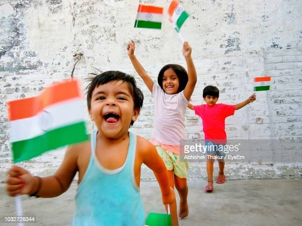 happy siblings with indian flags running against wall - indian flag stock pictures, royalty-free photos & images