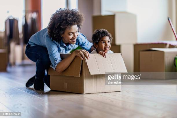 happy single black mother having fun with her daughter in carton box at new apartment. - home ownership stock pictures, royalty-free photos & images