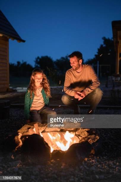 夜に裏庭で焚き火で幸せなシングル父と娘。 - 暖炉の火 ストックフォトと画像