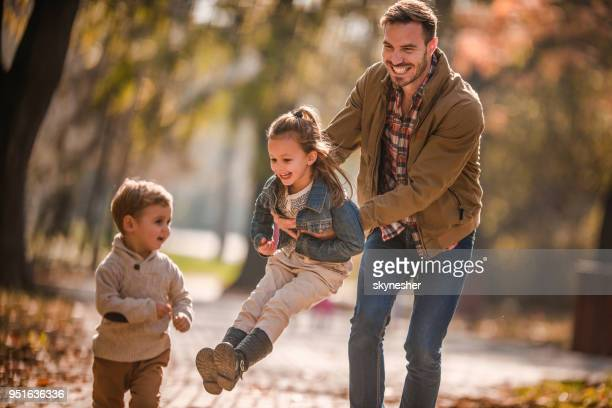 Happy single father having fun with his kids in autumn day.