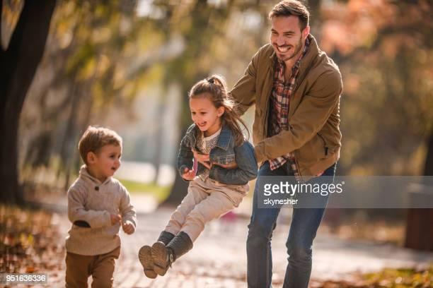 Padre soltero feliz divirtiéndose con sus hijos en el día de otoño.