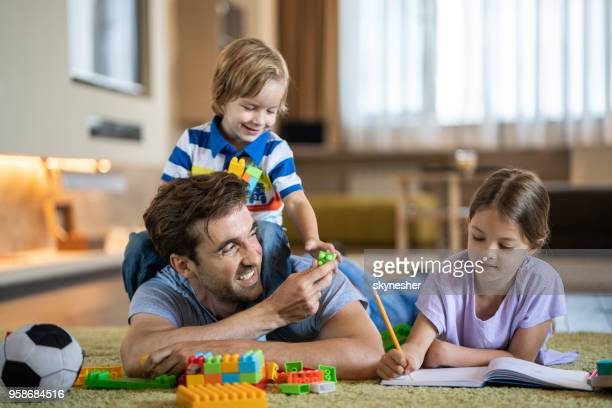 happy single father spending time with his kids at home. - the_writer's_block stock pictures, royalty-free photos & images