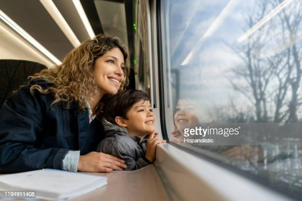happy single mother and son looking at the window view both smiling while traveling by train - train vehicle stock pictures, royalty-free photos & images