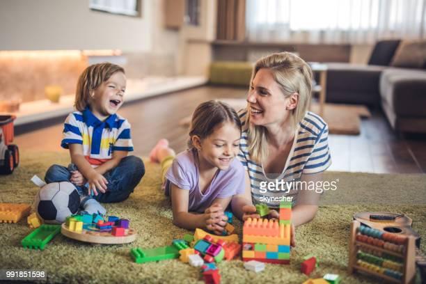 Glücklich allein erziehende mit ihren kleinen Kindern im Wohnzimmer spielen.
