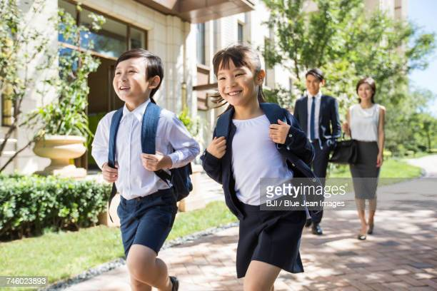 Happy sister and brother going to school