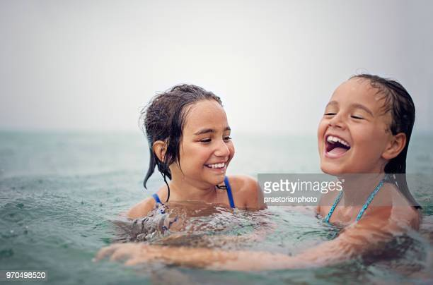 happy sisters are swimming in the ocean in a rainy day - bottomless girls stock photos and pictures